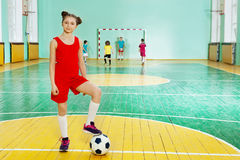 Sporty girl standing with soccer ball in futsal Stock Photography