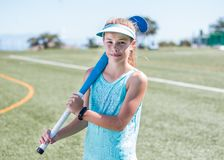 Sporty girl standing on sports field holding a blue hockey stick Royalty Free Stock Image