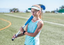Sporty girl standing on sports field holding a blue hockey stick Stock Photography