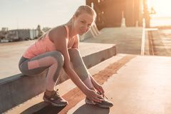 Sporty girl on street. Attractive sporty girl on street is sitting and tying her shoelaces, smiling and looking at the camera Royalty Free Stock Photos