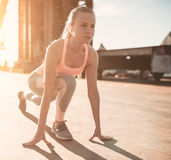 Sporty girl on street. Is on a crouch start. Ready to run Royalty Free Stock Image