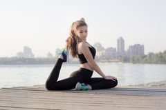 Sporty girl stretches at triangle pose during training workout o. Young pretty slim fitness sporty woman stretches at yoga poses during training workout Royalty Free Stock Photo