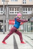 Sporty girl stretching outdoor on city street. Stock Photos