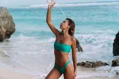 Sporty girl in swimsuit at beach pours clear water on herself from bottle. Beautiful woman drinks cool water on hot day. Concept bikini, summer, travel stock photography