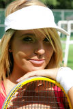 Sporty girl in tennis cap smiling. Sporty girl smiling in white tennis cap on court Royalty Free Stock Photo