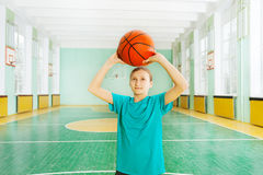 Sporty girl tossing ball in basketball rim Royalty Free Stock Images