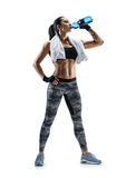 Sporty girl with towel on shoulders drink water. Resting time. Sporty girl with towel on shoulders drink water. Photo of muscular fitness model isolated on Stock Image