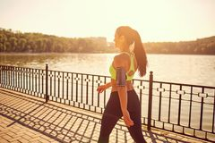 A sporty girl is walking in a sporting walk in the park. A sporty girl is walking in a sporting walk in the park by the lake Royalty Free Stock Photo