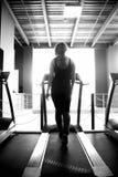 Sporty girl walks on treadmill Stock Images