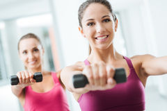 Sporty girls weightlifting at gym Stock Photography