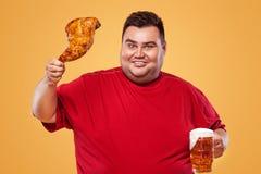 Sporty gruby mężczyzna przy oktoberfest, pijący piwo i jedzący kurczak nogę na żółtym tle obraz stock