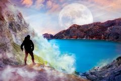Sporty guy against the background of the alien landscape. Mountains, the lake and sky with moon. Super Hero concept stock images