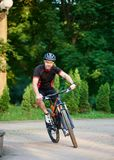 Male cyclist riding bike down park paved alley royalty free stock image