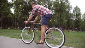Sporty guy cycling at the park road. Young handsome man riding a vintage bicycle outdoor. Healthy active lifestyle. Side Stock Photography