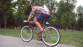 Sporty guy cycling at the park road. Young handsome man riding a vintage bicycle outdoor. Healthy active lifestyle. Side Royalty Free Stock Photo