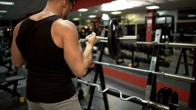 Sporty guy doing lift-ups with curl bar near stand in gym, pumping arm muscles. Stock photo royalty free stock photography