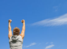 Sporty guy with his arms raised in joy Royalty Free Stock Photo