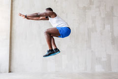 Sporty guy performing his jump upwards Royalty Free Stock Image