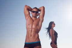 Sporty guy posing on the beach royalty free stock images
