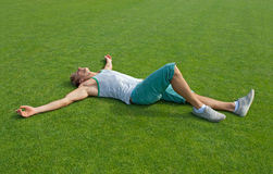 Sporty guy relaxing on green training field. Sporty young man laying on green training field with his arms spread, relaxing stock photos