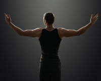 Sporty guy stands in the dark and shrugs Stock Image