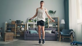 Sporty guy student jumping rope in apartment exercising alone enjoying sports stock video