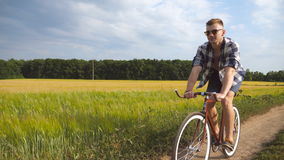 Sporty guy in sunglasses cycling along country trail outdoor. Young smiling man riding vintage bicycle at rural road stock footage