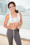 Sporty happy brunette holding skipping rope Royalty Free Stock Image