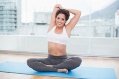 Sporty happy brunette stretching on exercise mat Royalty Free Stock Photos