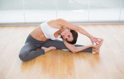 Sporty happy brunette stretching on the floor Royalty Free Stock Photography