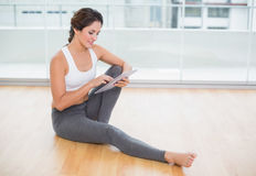 Sporty happy brunette using tablet sitting on the floor Stock Images