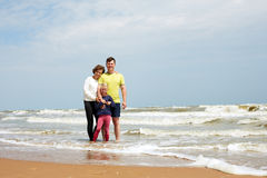 Sporty happy family on tropical beach in summer day. Family on tropical beach in cloudy summer day stock photography