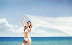 A sporty and happy woman posing with blowing silk on the beach Stock Image