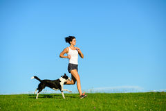 Sporty happy woman running with dog outdoor. Woman and dog running and exercising outdoor at grass field on summer or spring. Happy female athlete training with Stock Photo
