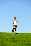 Sporty happy woman running with dog outdoor Royalty Free Stock Photos