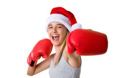 Sporty happy young girl wearing christmas santa hat with fighting gloves isolated Stock Image