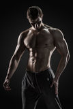 Sporty healthy man posing and showing his perfect boddy. Sporty and healthy man posing and showing his perfect boddy on black background Stock Photography