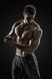 Sporty healthy man posing and showing his perfect boddy. Sporty and healthy man posing and showing his perfect boddy on black background Stock Photos