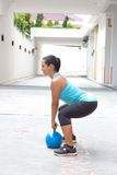 Sporty hispanic woman in blue attire holding a blue kettlebell in dead lift post outdoors. Beautiful sporty hispanic woman in blue attire holding a blue Royalty Free Stock Photos