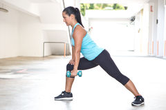 Sporty hispanic woman in blue  demostrating the rowing routine with blue dumbbell outdoors Stock Image