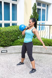 Sporty hispanic woman in blue training with kettlebell doing the clean routine Royalty Free Stock Images