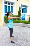 Sporty hispanic woman in blue training with kettlebell doing the swing routine Royalty Free Stock Image