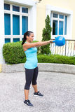 Sporty hispanic woman in blue training with kettlebell showing the swing routine Stock Photos