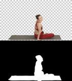 Представление лотоса йоги Sporty женщины практикуя, поворачивающ к камере и усмехающся, канал альфы стоковое фото rf