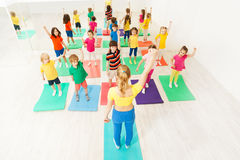 Sporty kids doing gymnastic exercises with coach. Big group of sporty kids doing gymnastic exercises with female instructor, holding their arms upwards, in Royalty Free Stock Images