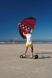 Sporty kite girl. A sporty young woman holding a kite on a skateboard on the beach racing. Red kite, yellow shorts, blue sky. The sea at the background with low royalty free stock photo