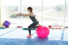 Sporty kobieta robi ćwiczeniom z dysponowaną piłką w gym Poj?cie: styl ?ycia, sprawno?? fizyczna, aerobiki i zdrowie, zdjęcia royalty free