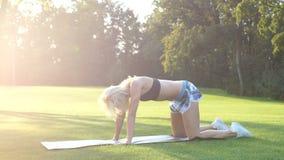 Sporty kobieta robi rozciąganiu ćwiczy plenerowego Sprawności fizycznej dziewczyna robi lunges w parku przy latem Trening przy sł zdjęcie wideo