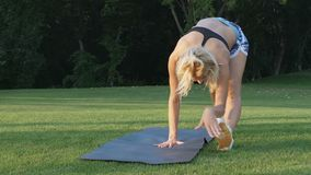 Sporty kobieta robi rozciąganiu ćwiczy plenerowego Sprawności fizycznej dziewczyna robi lunges w parku przy latem Trening przy sł zbiory wideo