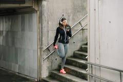 Sporty kobieta używa smartphone dla słuchającej muzyki podczas gdy rozciągający obrazy stock